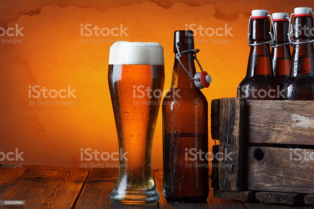 Beer glass with wooden crate with bottles stock photo
