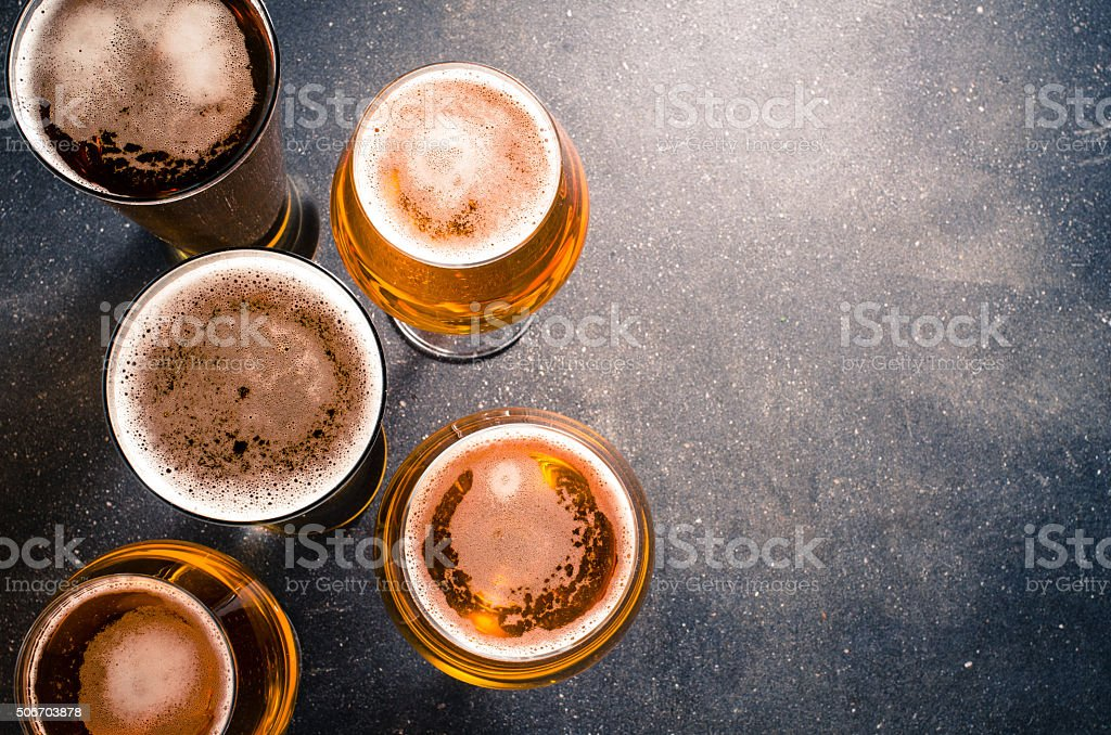 Beer glasses on dark table stock photo