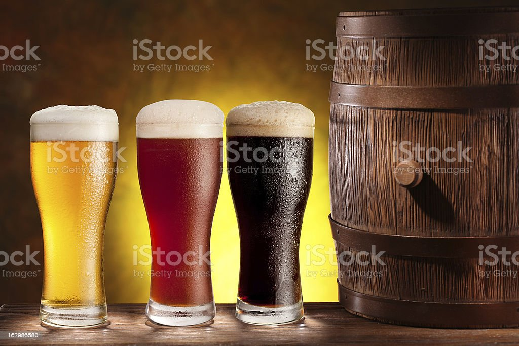Beer glasses with a wooden barrel. royalty-free stock photo