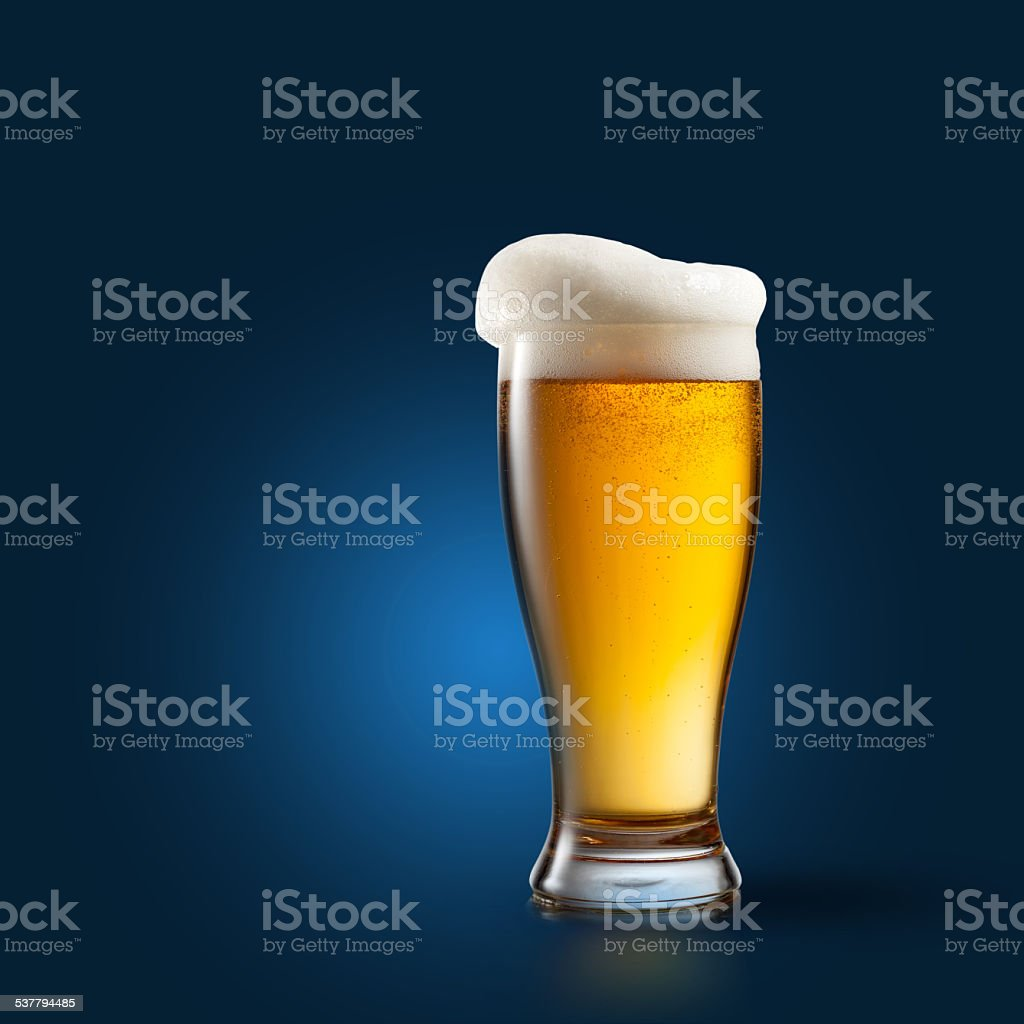 Beer in glass on blue stock photo