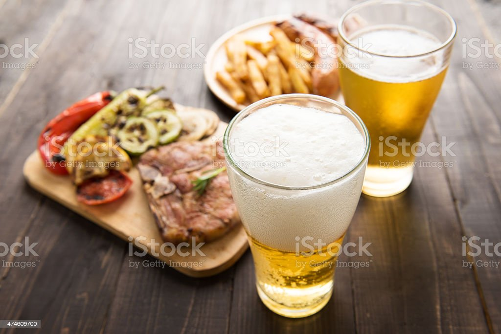 Beer in glass with gourmet steak and french fries stock photo