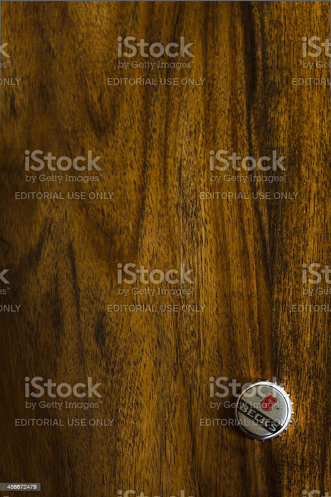 Beer metal cap on a old wooden table. stock photo