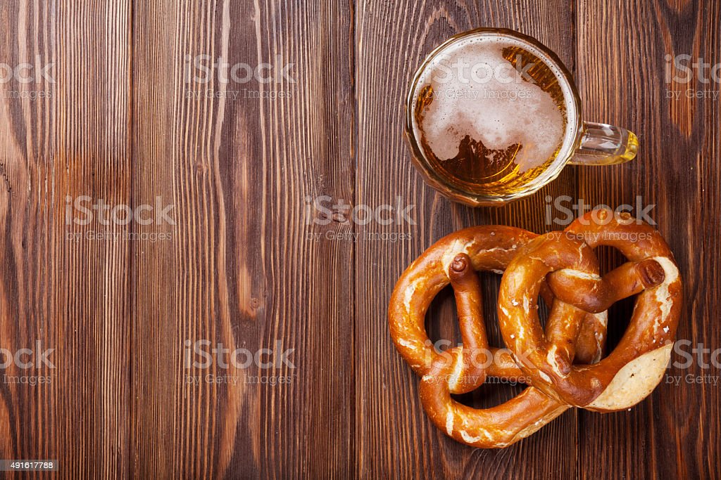 Beer mug and pretzel on wooden table stock photo