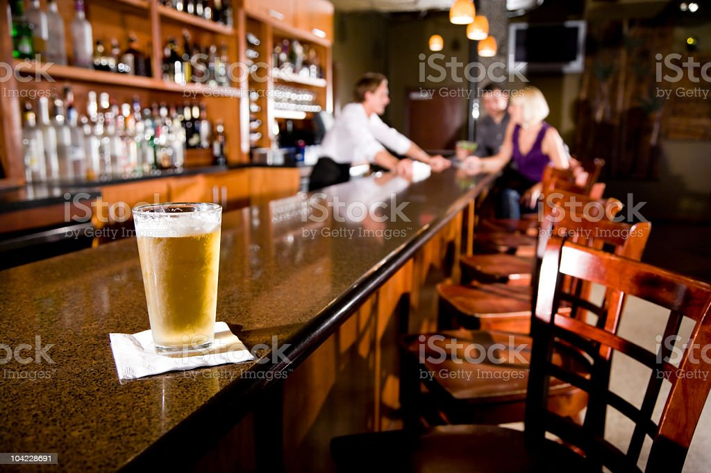 Beer mug on bar counter, bartender and customers in background stock photo