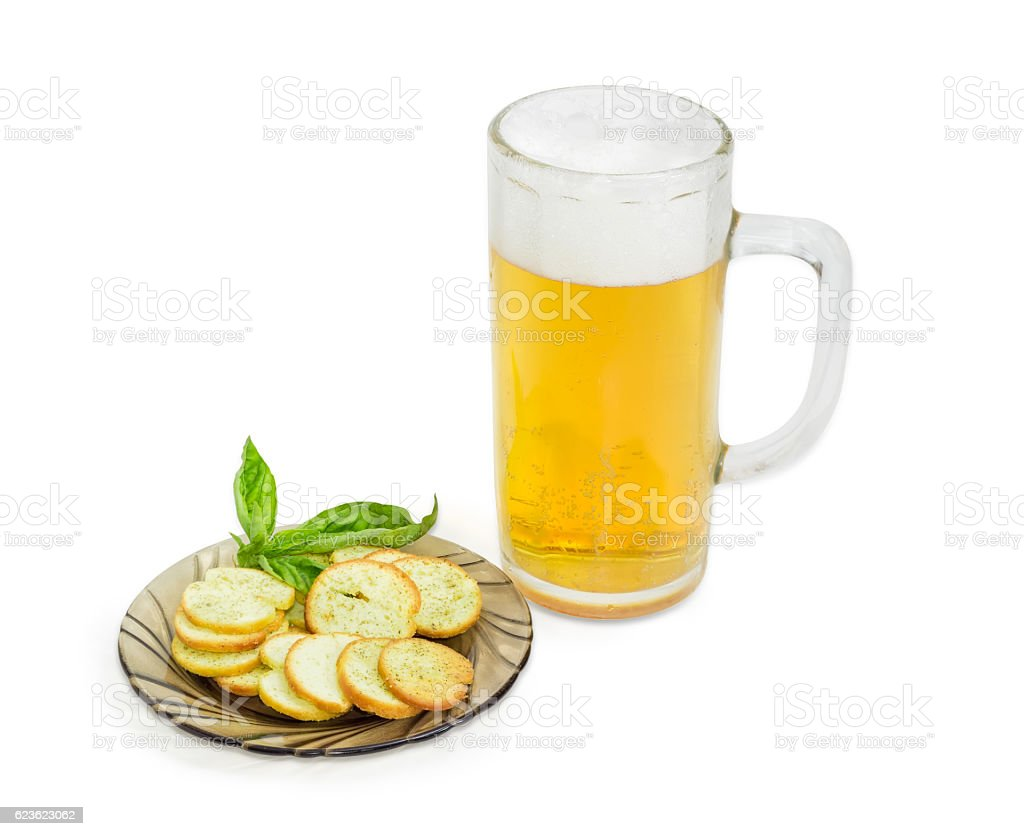 Beer, rusks with basil on a saucer on light background stock photo