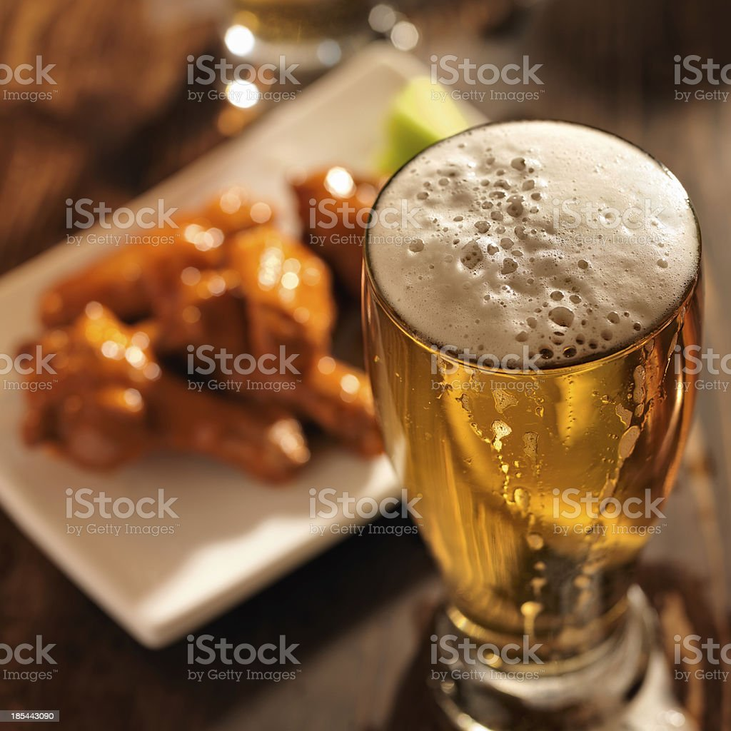beer with chicken wings in background. stock photo
