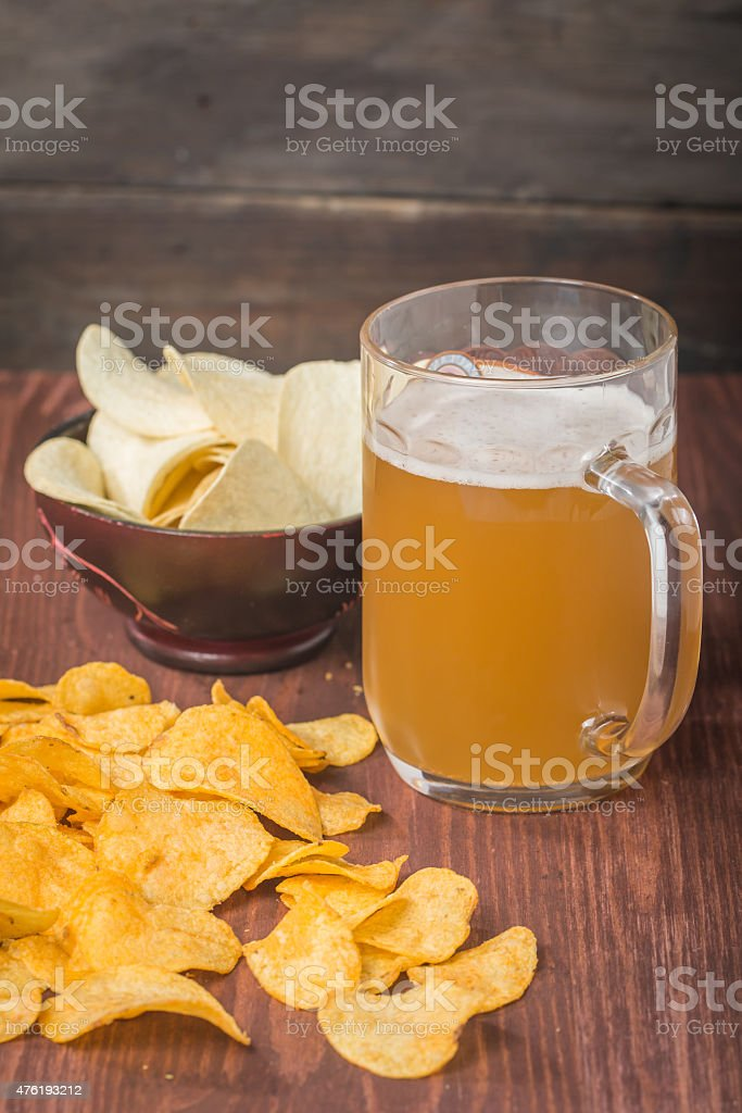 Beer with foam in glass mug and potato chips stock photo