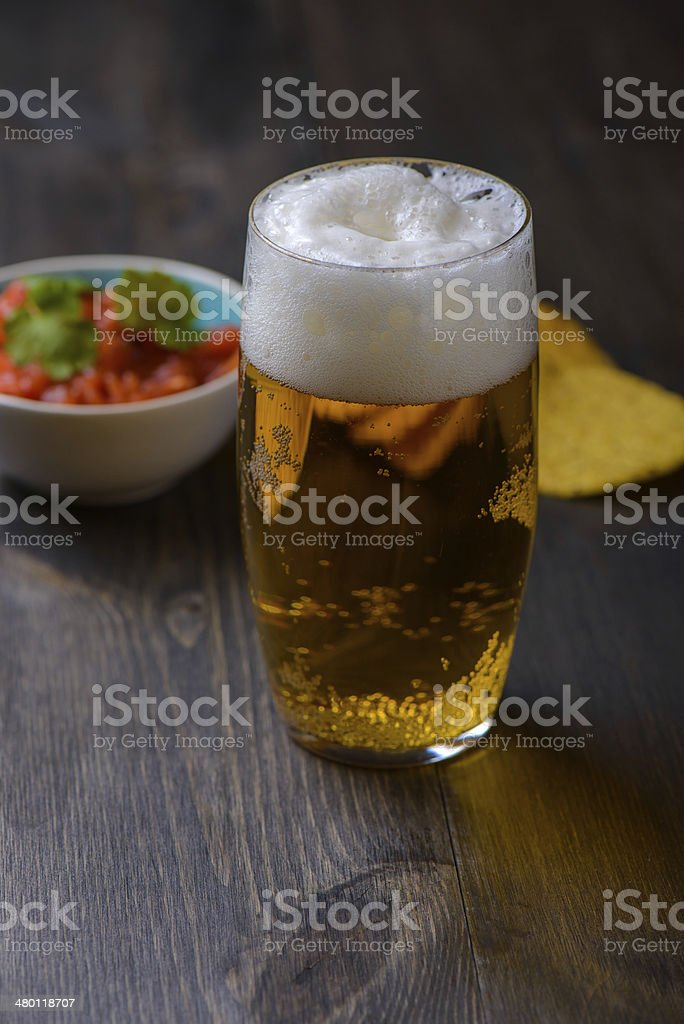 Beer with nachos and salsa in the background stock photo