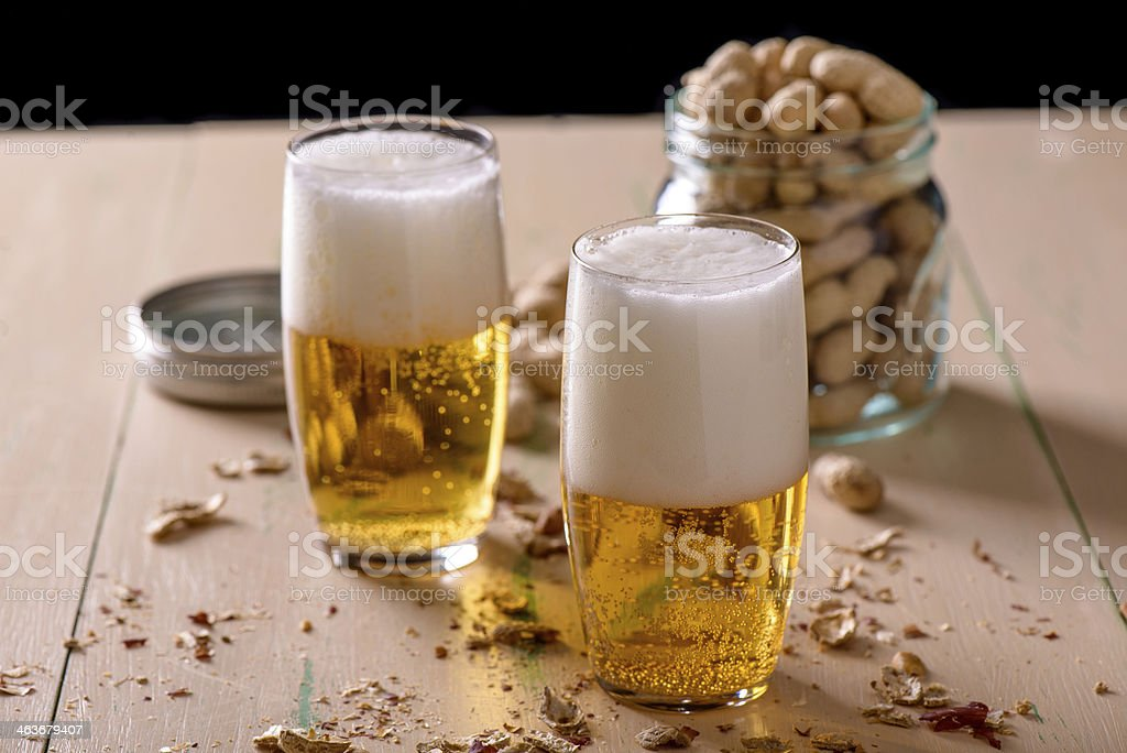 Beer with peanuts on old wood table stock photo