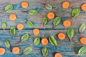 Beet leaves and carrots on white background. Top view, Flat