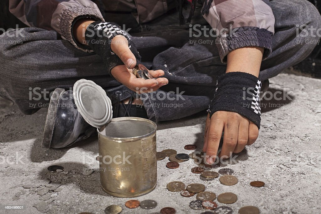 Beggar child counting coins sitting on damaged concrete floor stock photo