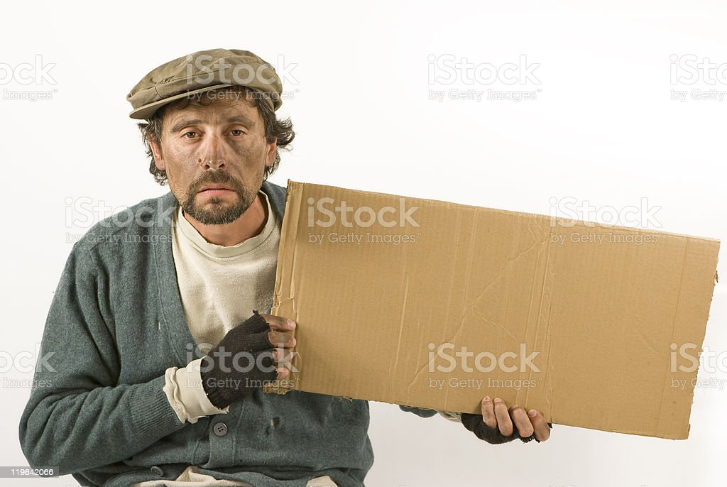 Beggar Holding a Cardboard and Wearing Worn Clothing stock photo