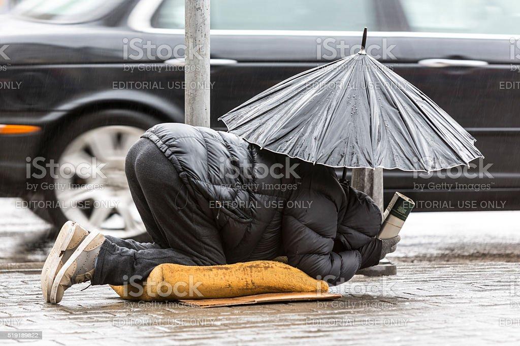 Beggar in the rain with umbrella car stock photo