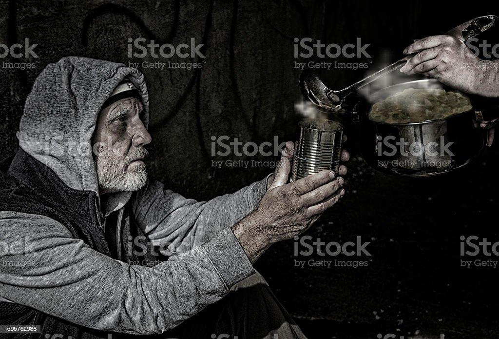 Beggar receiving soup stock photo