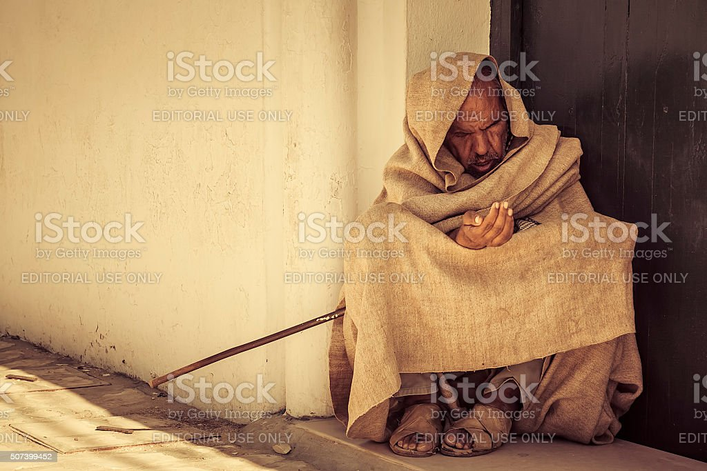 Beggar sleeps with a gesture for handouts. stock photo