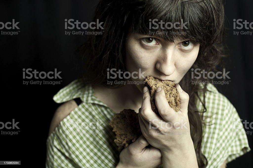 beggar woman eating bread stock photo