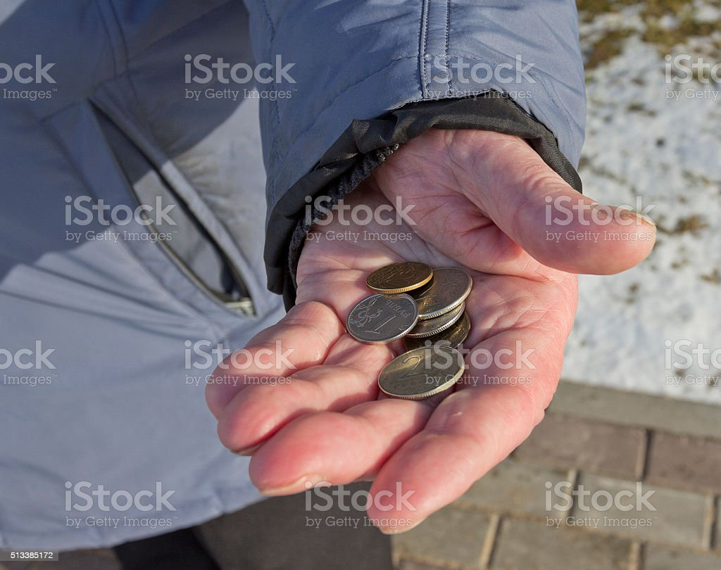 Beggar's hand with coins stock photo