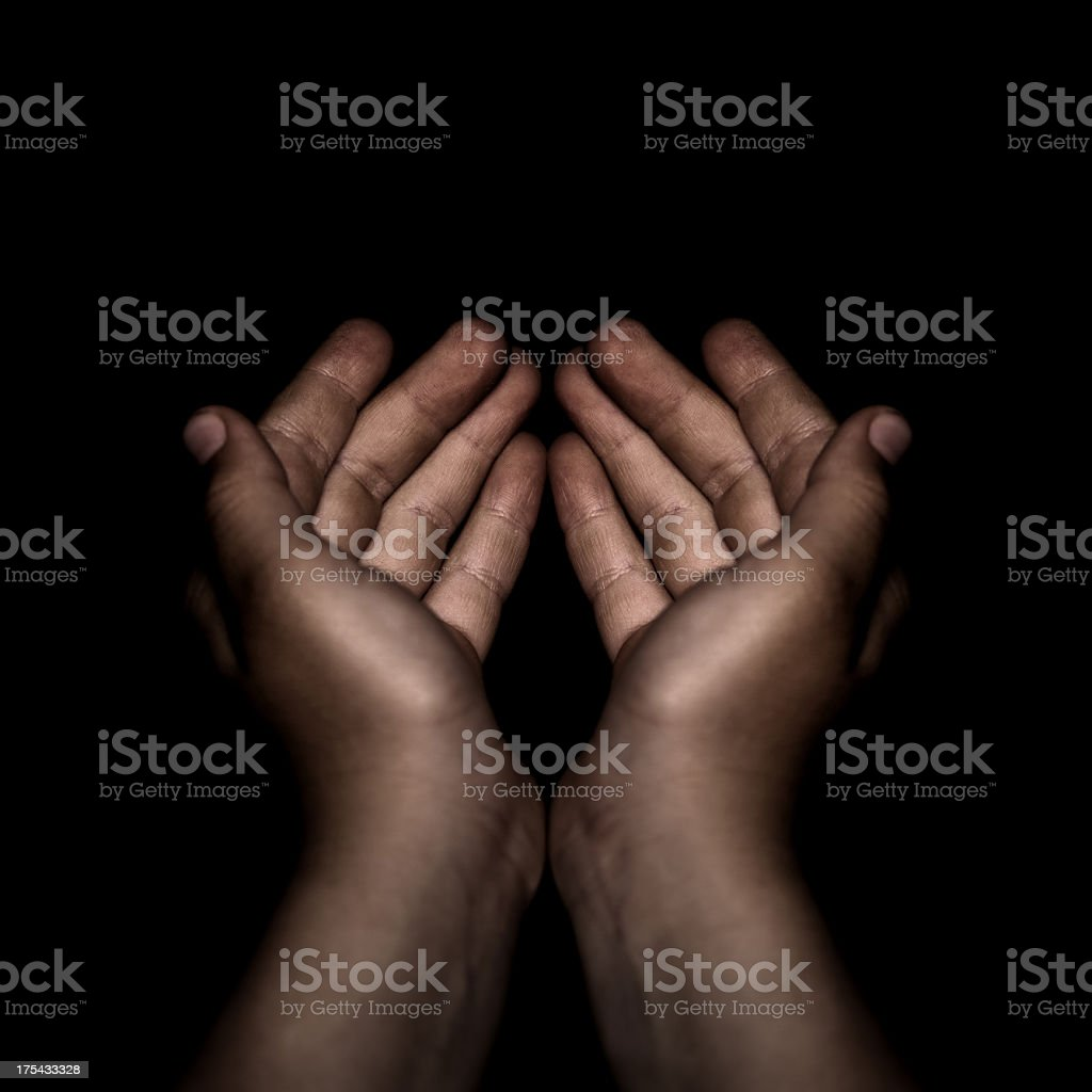 Begging. Child's hands isolated on black background. stock photo