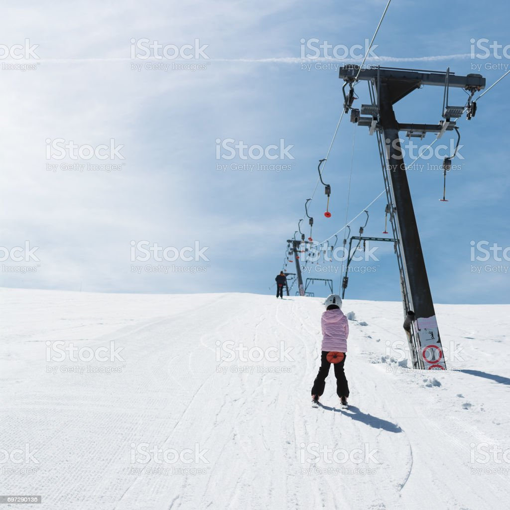 Beginner little girl with skis ascends with ski lift stock photo