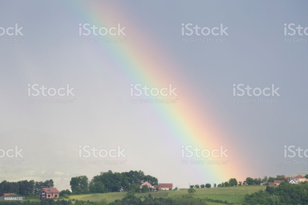 Beginning or the end of a beautiful rainbow above village stock photo