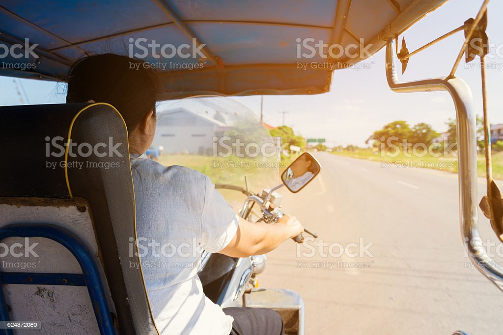 Behind of Woman is driving tuktuk. stock photo