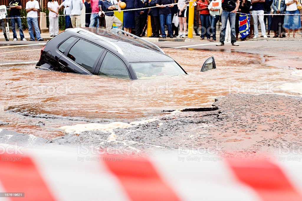 Behind police cordon tape, a car slides into  muddy sinkhole stock photo