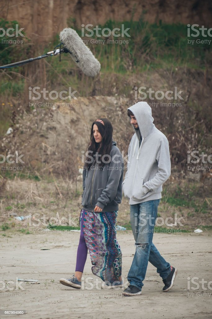 Behind scene. Actor and actress in front of boom microphone stock photo