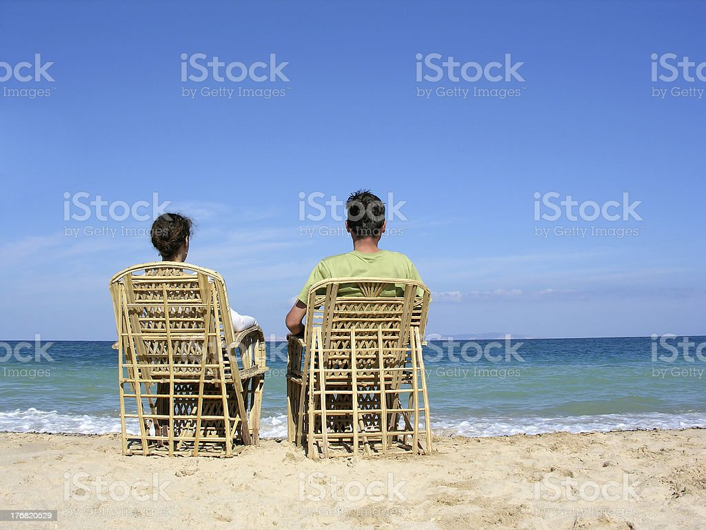 behind sitting couple on beach royalty-free stock photo