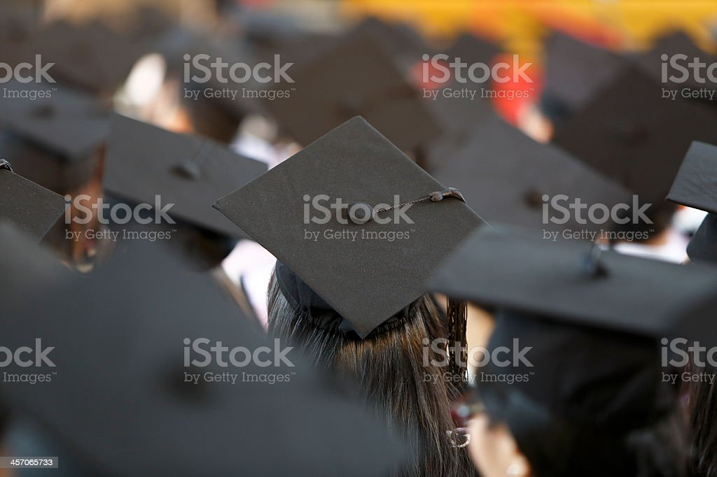 Behind view of graduates at ceremony wearing mortar hats stock photo