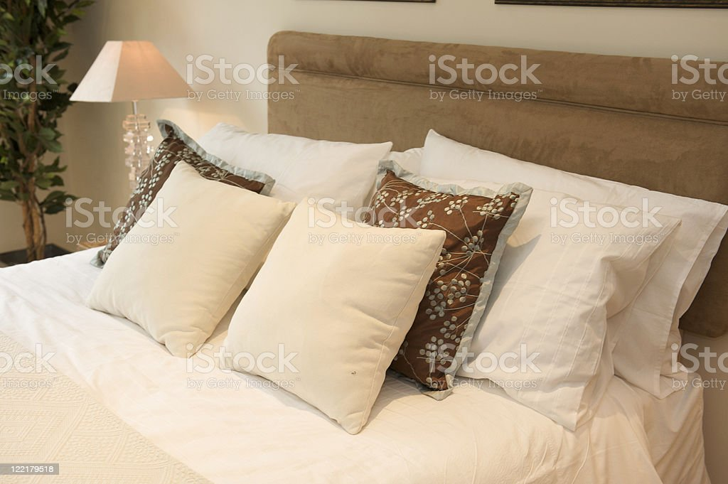 Beige bed decor royalty-free stock photo