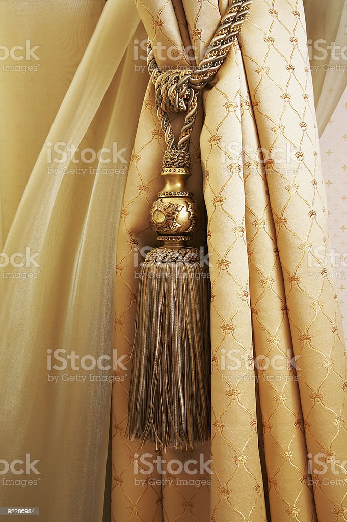 Beige curtains with a stringy gold ornament royalty-free stock photo