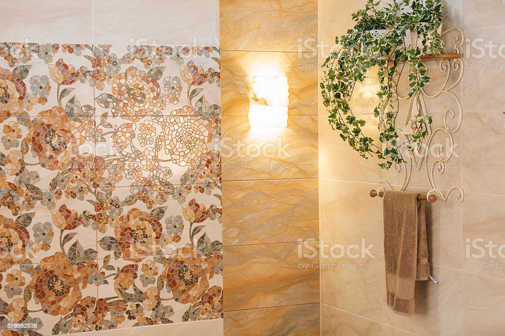 Beige floral bathroom with mosaic wall stock photo