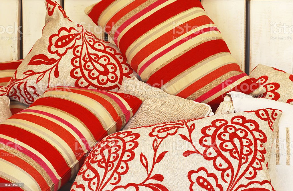 Beige pillows with warm colored stripes and flowers patterns royalty-free stock photo