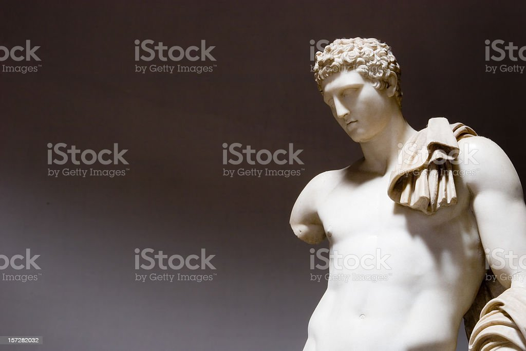 A beige roman statue on a gray background. royalty-free stock photo