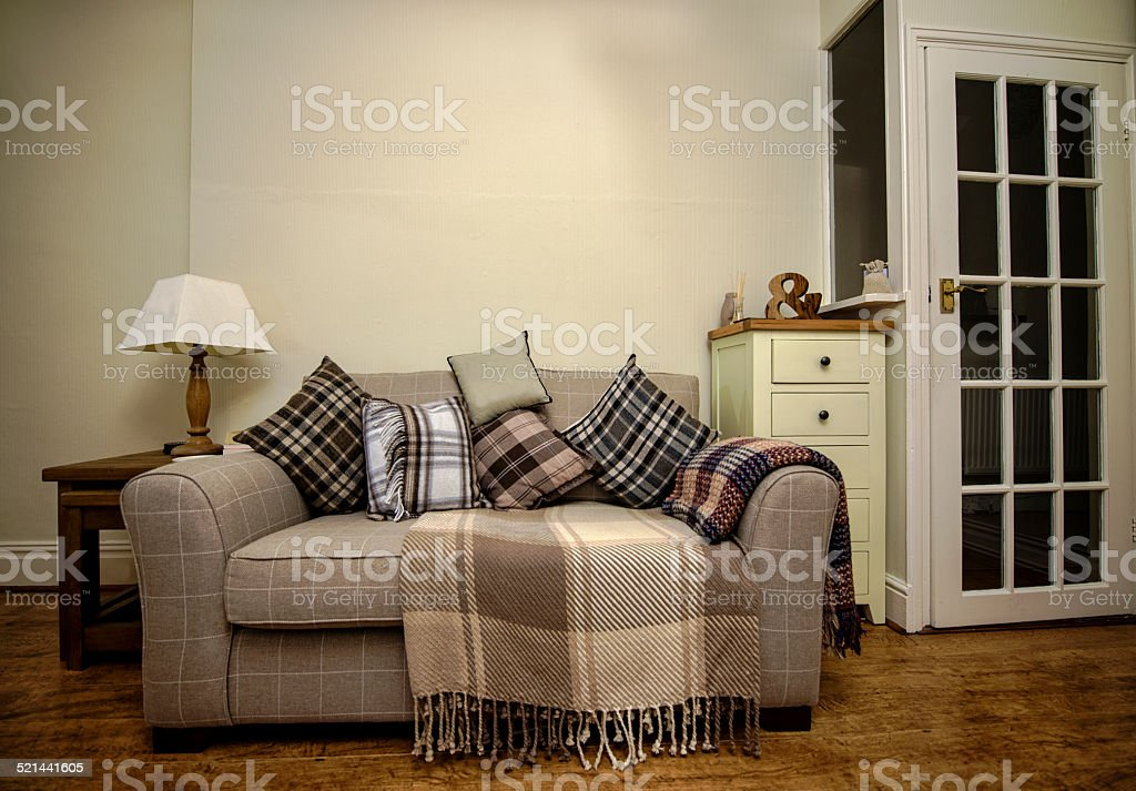 Beige sofa with cusions, rug, table lamp and cabinet stock photo