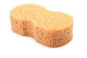 A beige sponge with holes in on a white background