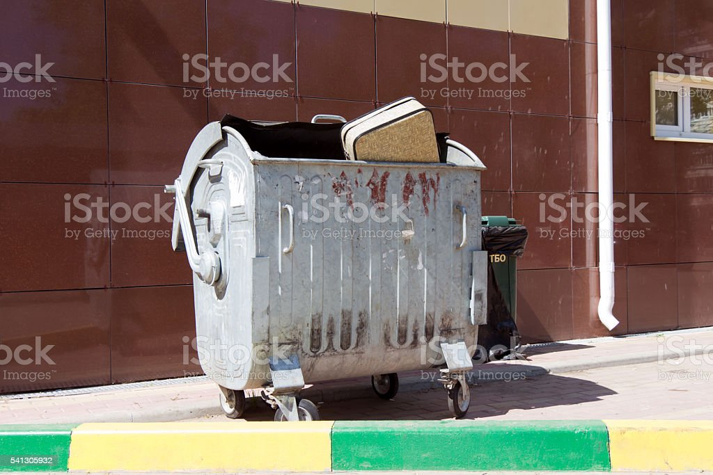 Beige suitcase thrown in a metal trash can standing against stock photo