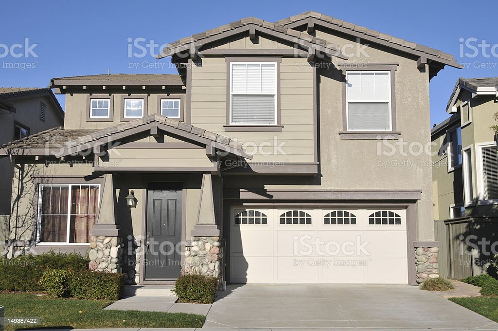 Beige two-story single family home with garage and driveway stock photo