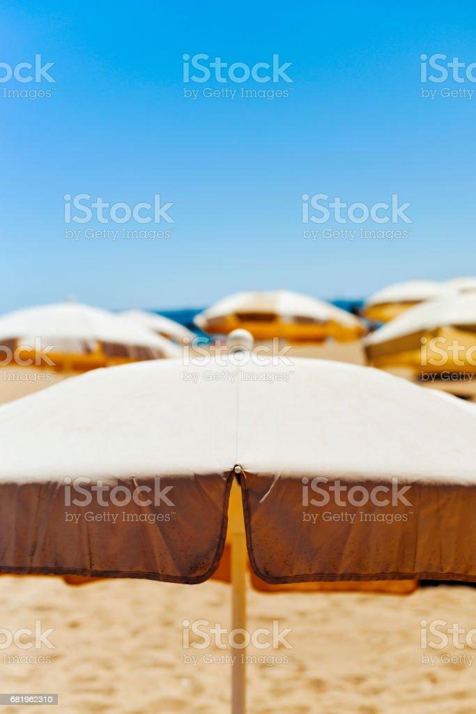 beige umbrellas in a quiet beach stock photo