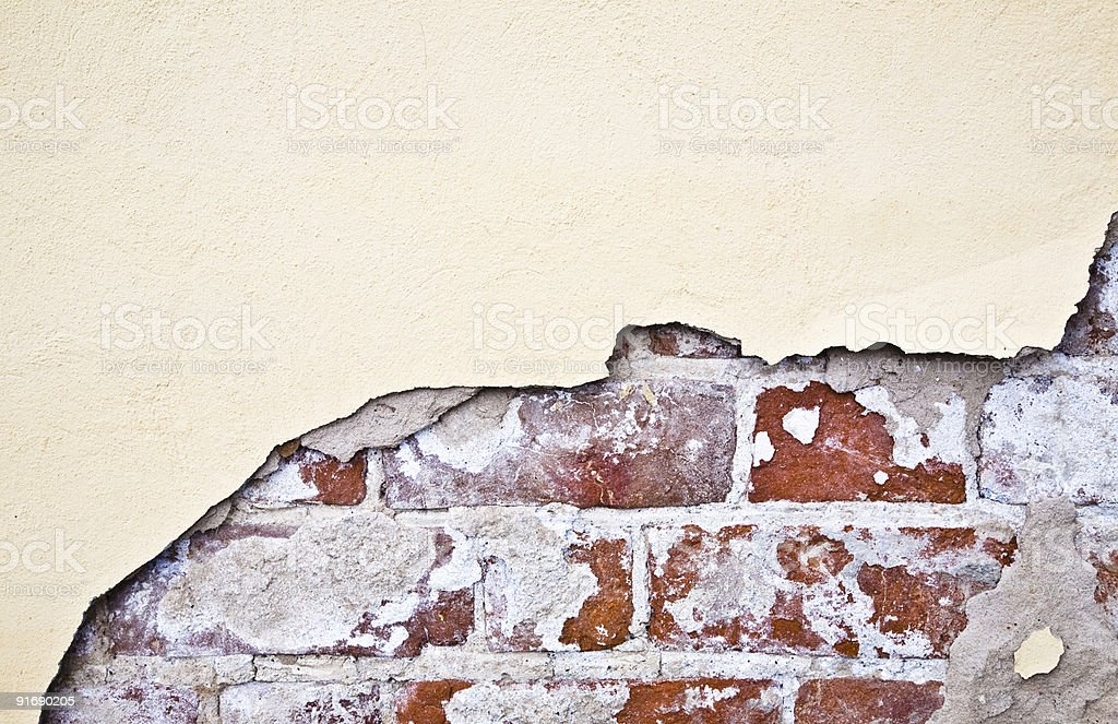 A beige wall broken to reveal a brick wall underneath royalty-free stock photo
