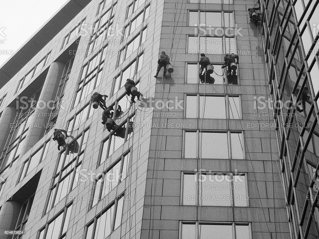 Beijing window cleaners at the top floors of office building stock photo