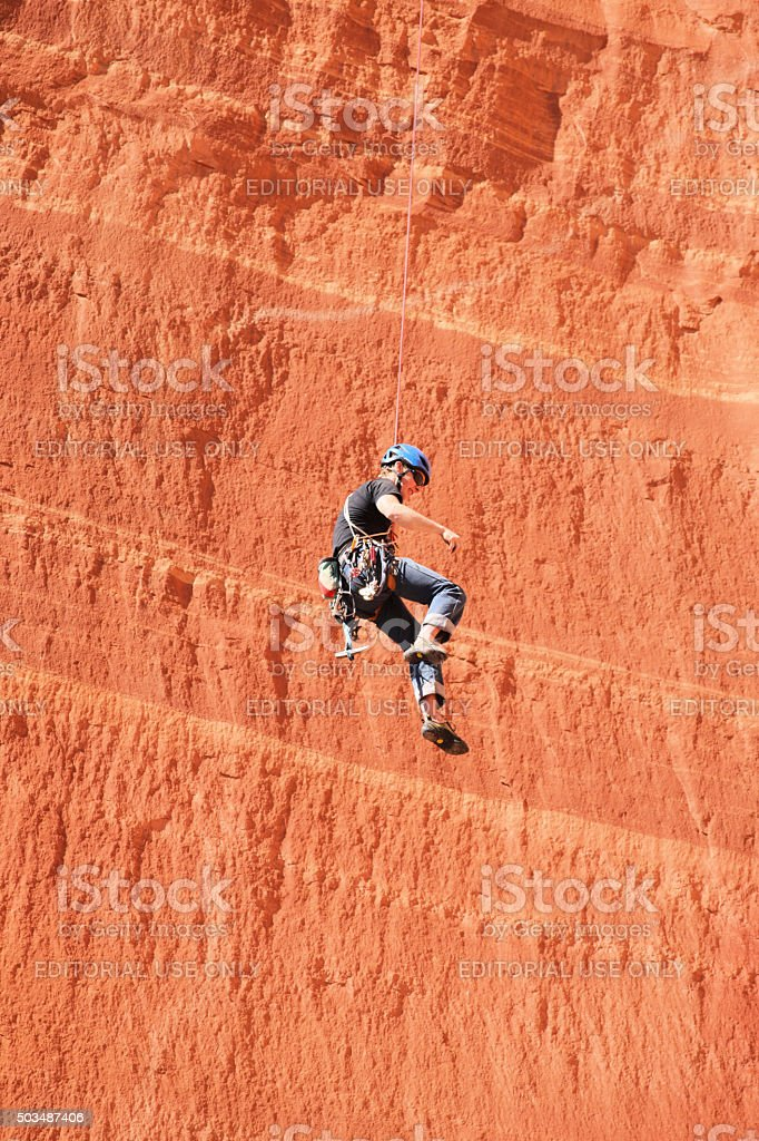 Belaying Rock Climber Rappelling Cliff Face stock photo