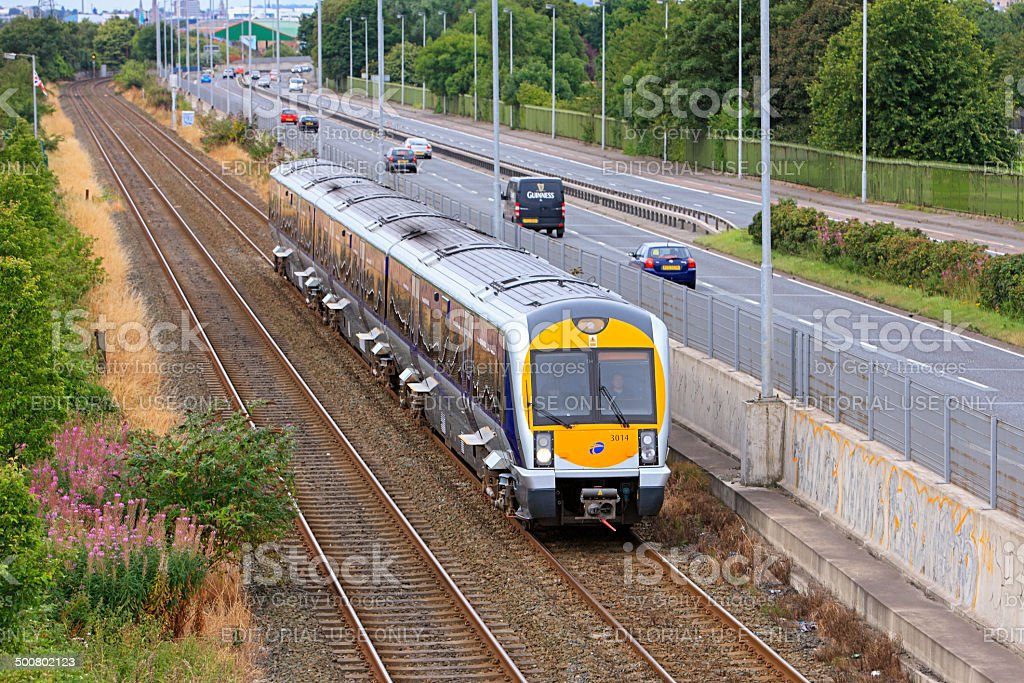Belfast commuter train approaching station with adjacent highway traffic stock photo