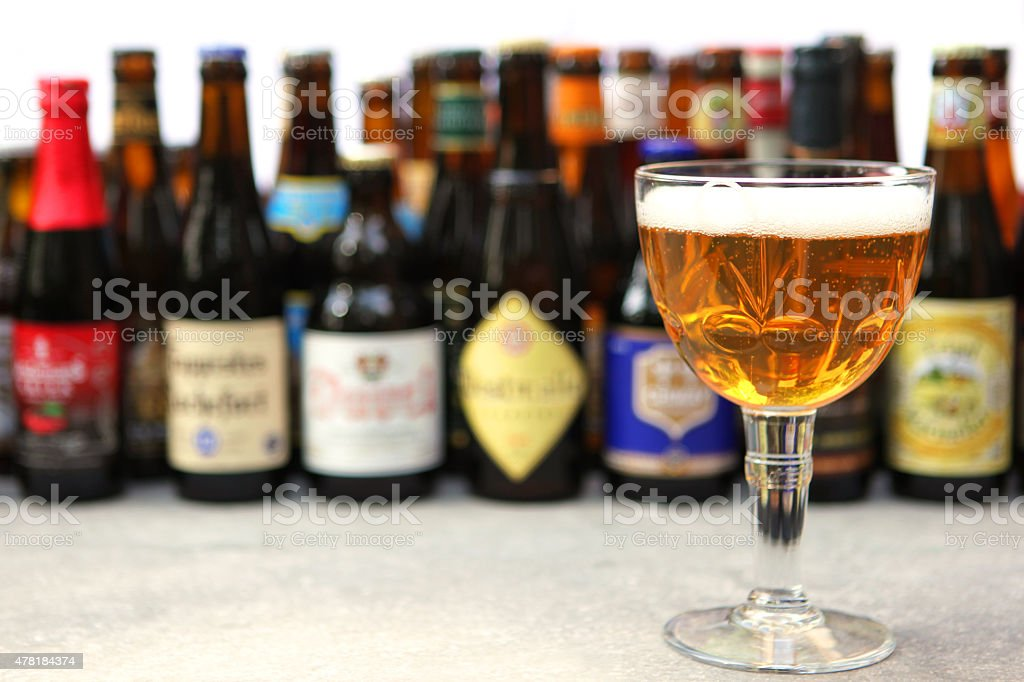 Belgian Beer Glass and Variety of Bottles in the Background stock photo