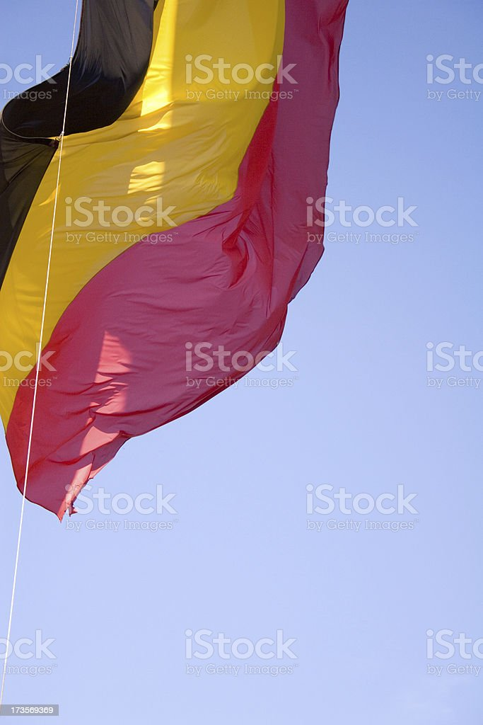 Belgian flag up close against blue sky royalty-free stock photo