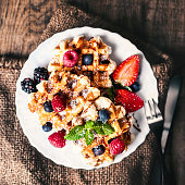 Belgian waffles with strawberries, blueberries and syrup on wood