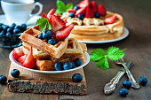Belgian waffles with strawberries, blueberries and syrup