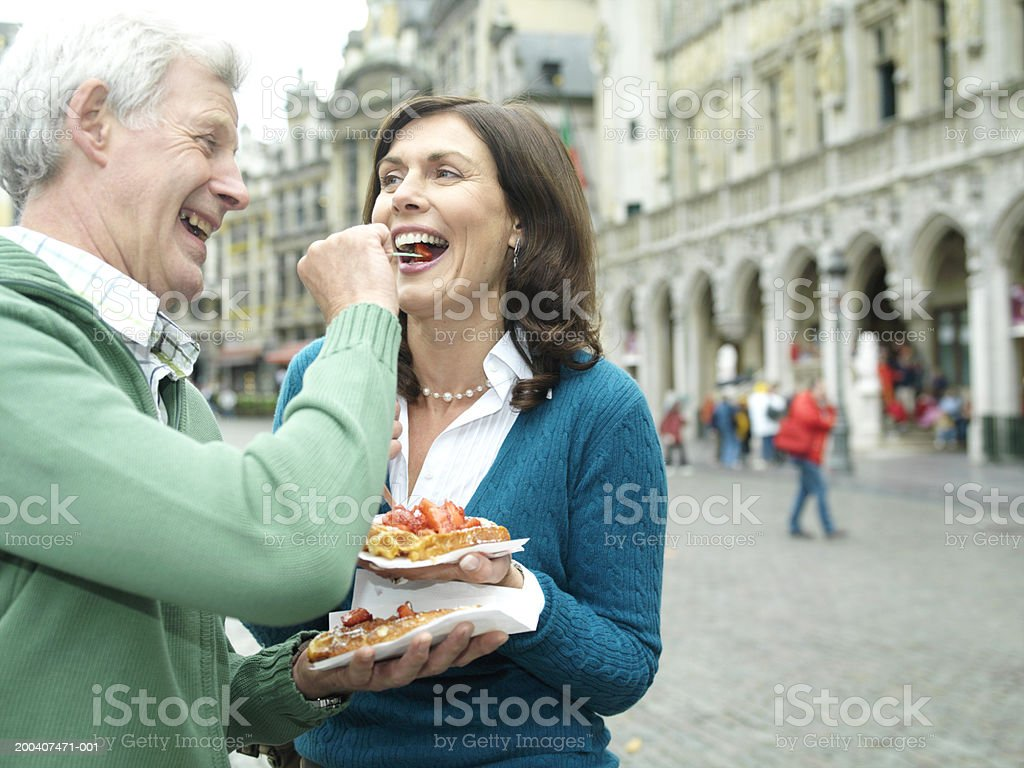 Belgium, Brussels, man feeding woman, smiling royalty-free stock photo