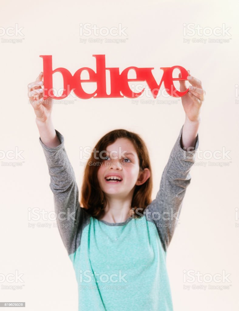 'believe' says three-dimensional sign held aloft by smiling pre-teen girl stock photo