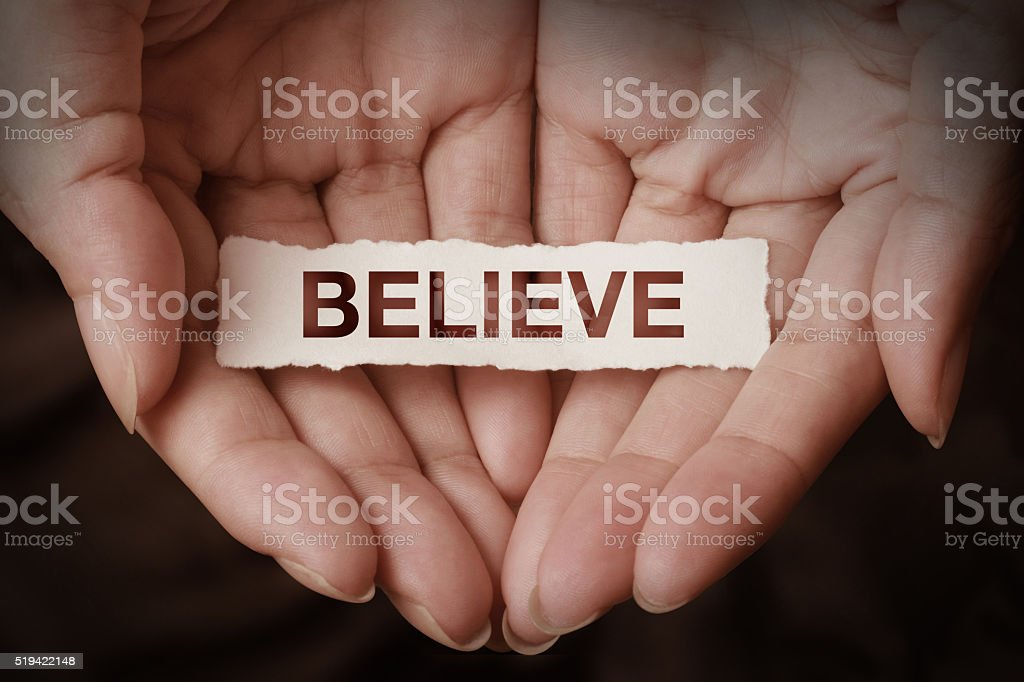 Believe text on hand stock photo